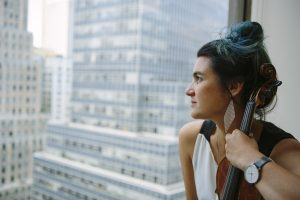 Alicia looks out the window of a wall street building holding her violin