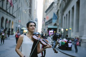 Alicia plays violin on Wall Street cobblestones