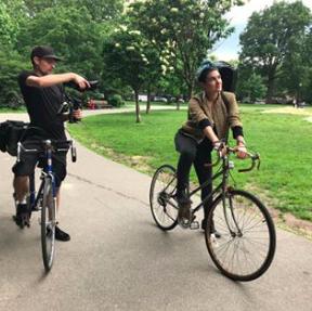 bike-riding cameraman films Alicia as she rides a bike