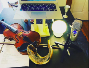 desk with laptop, violin, microphone and shofar